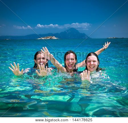 Three beautiful attractive young women having fan on the beach