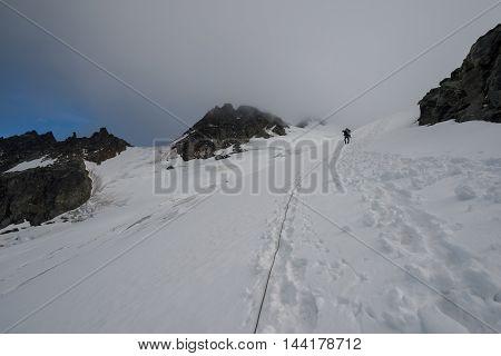 A mountain climber climbs over a glacier early morning
