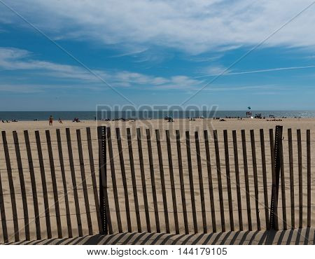 View of the beach through a fence
