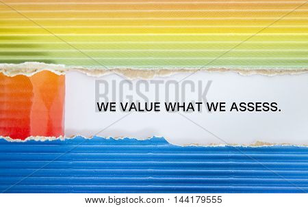 WE VALUE WHAT WE ASSESS message written under torn paper.