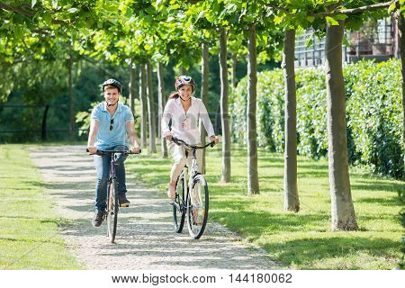 Young Smiling Couple Wearing Helmets On Theirs Heads Riding On The Bicycles In Park