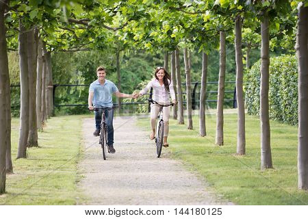Young Happy Couple Holding Each Other's Hand While Riding On Bicycle In Park