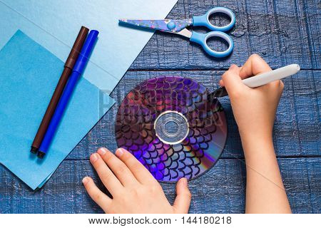 Making homemade toy fish from the CD. Paper CD scissors markers on a blue wooden table. Handmade children's project. Step by step photo instructions. Step 1: The child draws fish scales