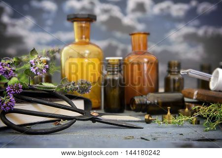 natural medicine healing herbs scissors and apothecary bottles on blue rustic wood against a dark sky with clouds selected focus and narrow depth of field