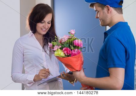A Young Woman Signs For Receipt Of A Bouquet Of Flowers