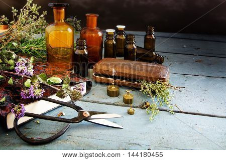 preparing natural medicine healing herbs scissors and apothecary bottles on rustic blue painted wood with copy space vintage style selected focus
