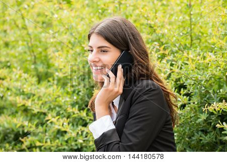 Happy Young Businesswoman Sitting On Bench Talking On Mobile Phone At Park