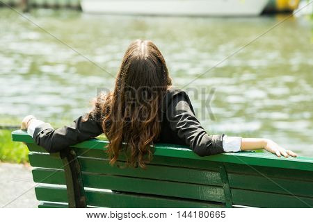 Rear View Of A Businesswoman Sitting On Bench