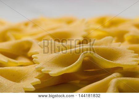 Bow tie pasta Close up. Farfalle pasta. Farfalle bows italian pasta. Farfalle - bow shaped pasta background.