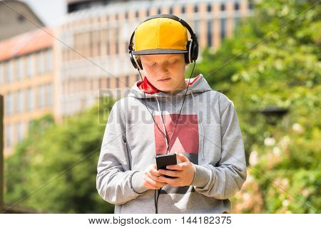 Boy Wearing Yellow Cap Using Mobile Phone While Listening To Music