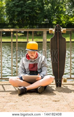 Boy Wearing Cap Using Digital Tablet In Front Of Railing