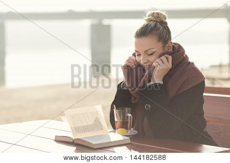 Young beautiful blond sitting in an outdoor cafe by the river drinking tea and reading a book on a sunny autumn day