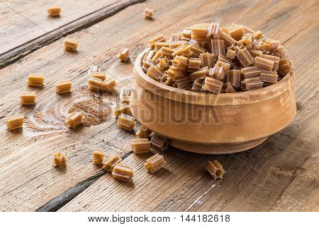 Raw pasta of buckwheat flour in a wooden bowl on the old wooden table. Gluten-free products. The source of vitamins and minerals. The concept of healthy and vegetarian food