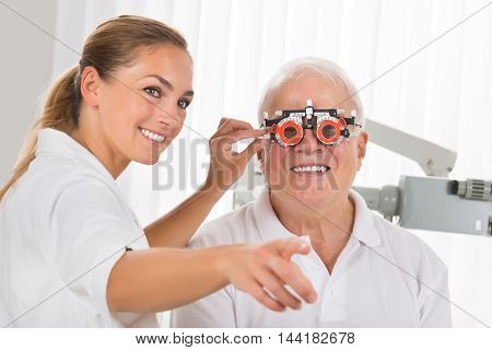 Smiling Young Female Optometrist Checking Senior Male Patient's Vision With Trial Frame