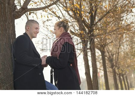 Young couple in love standing next to a tree on an autumn vacation enjoying the nature and holding hands
