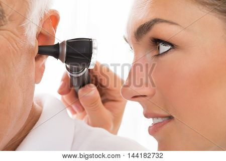 Close-up Of Female Doctor Examining Patient's Ear With Otoscope