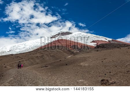 Cotopaxi volcano with some climbers ascending by its sandbanks to refuge