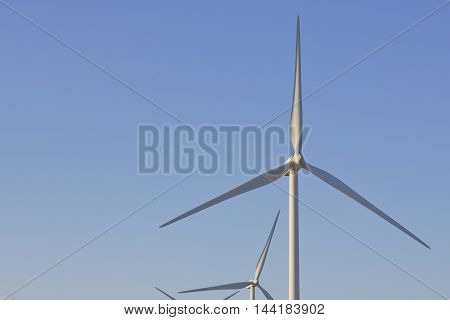 Windmill blades with a cloudless sky background.