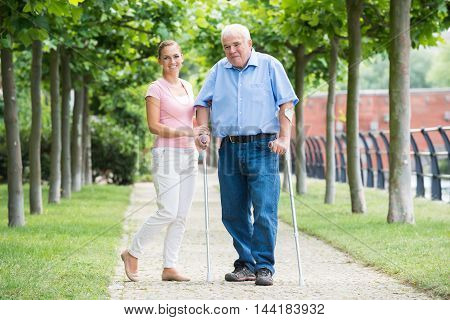 Portrait Of A Smiling Young Woman With Her Disabled Father Standing In Park