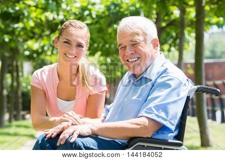 Portrait Of A Smiling Young Woman With Her Disabled Father On Wheelchair