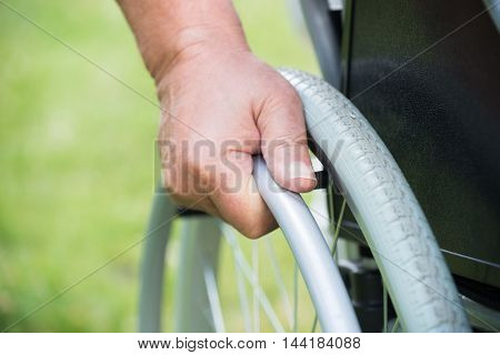 Close-up Of A Disabled Man Pushing Wheel Of Wheelchair