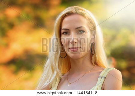Autumnal portrait of a beautiful long haired blond lady under sunlight
