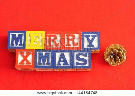 Merry Xmas spelled with Alphabet blocks and an acorn on a red background