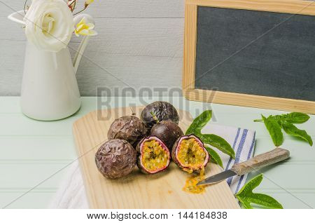Passion fruits with leaves knife and white flowers in jar on the vintage wooden table.