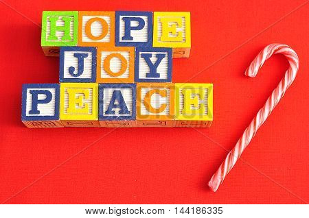 Xmas Hope and Joy spelled with Alphabet blocks on a red background with a candy cane