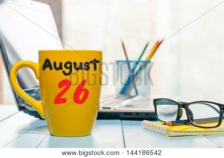 August 26th. Day 26 of month, calendar on cappuccino yellow cup at traveller workplace background. Summer time. Empty space for text.