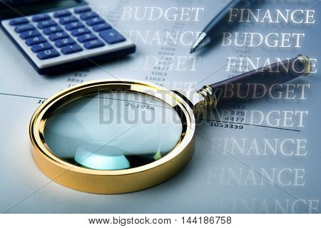 work on the budget with a magnifying glass a calculator