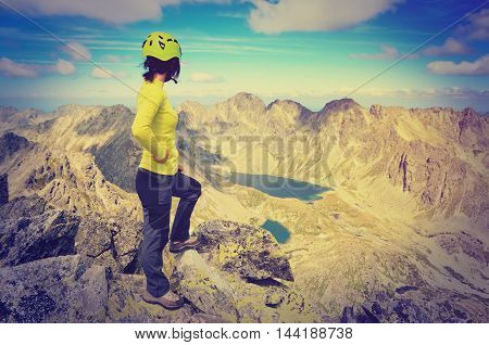 Tourist admiring the beautiful mountain valley in vintage style.. Young woman on a mountain top in High Tatra Slovakia.