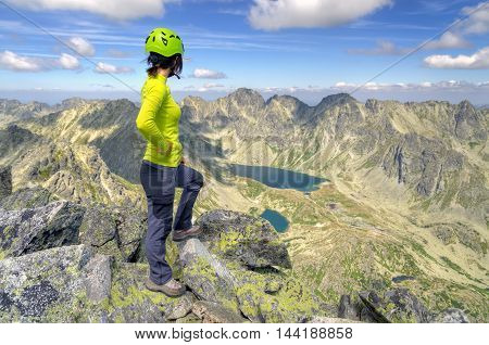 Tourist admiring the beautiful mountain valley. Young woman on a mountain top in High Tatra Slovakia.