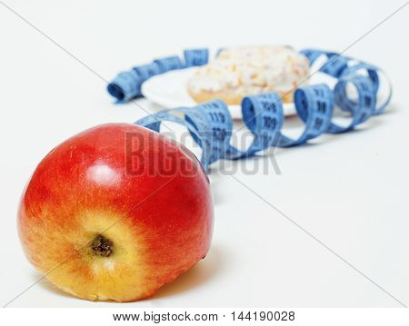 New diet concept, measurement tape in shape of question mark between red apple and doughnut on a white background.