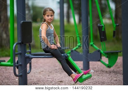 Little girl is engaged in sports equipment outdoor.