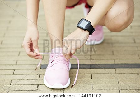 young woman runner with wearable fitness device tying shoelace close-up.