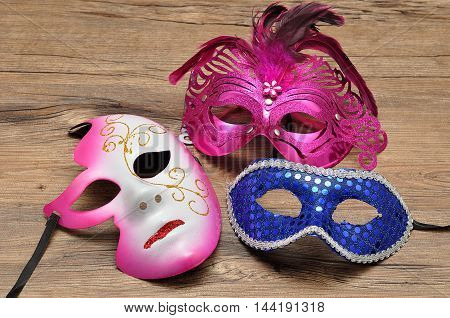A collection of masks isolated on a wooden background