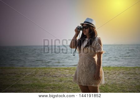 woman take photo with film camera by sea beach ocean on twilight time sunset on beach in white dress and white hat