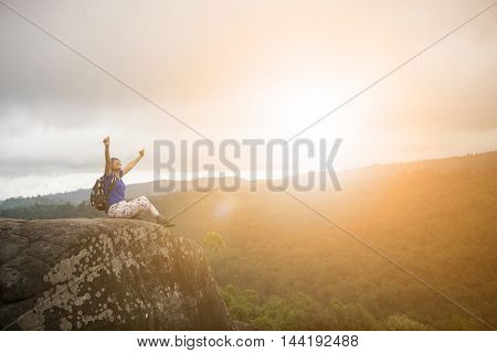 backpacker woman relaxing and victory hand rising on rock cliff and sun set sky above