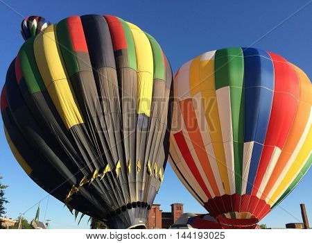 Two hot air balloons are inflated as a third flies in the distance.