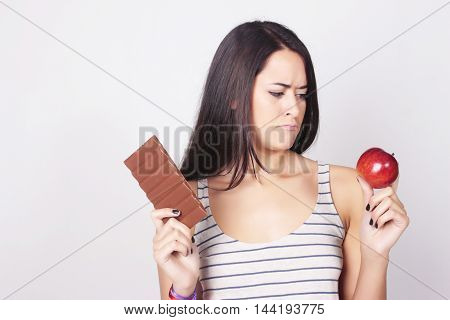 Young Woman Deciding Between Eating Chocolate Or Apple