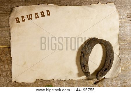 Old horseshoe and the announcement of the award on a wooden background
