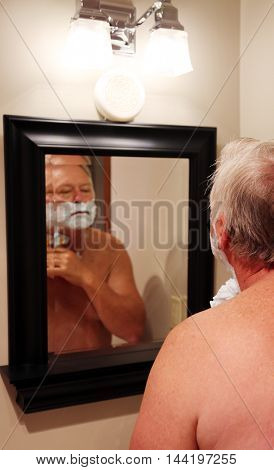 A man shaves in a mirror