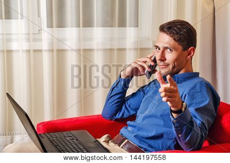 Man works for laptop. Businessman discussing on a cell phone call details of important transactions and shows the index finger at the camera. Freelancer at work. I choose you.