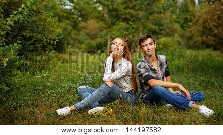 Loving couple teens sitting on the lawn in the park. Girlfriend and boyfriend together. First love. He falls in love. Date.