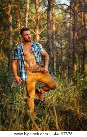 Lumberjack with ax walking through forest. Woodcutter in unbuttoned shirt in the coniferous forest. Felling trees. Logging. Manual labor. Brutal man.