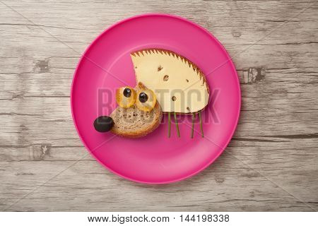 Confused hedgehog made of bread and cheese on plate and board