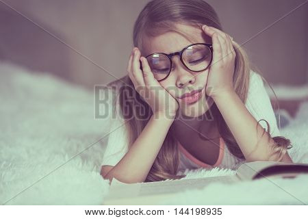 Portrait of sad little girl lying on bed at the day time. Concept of sad childhood.