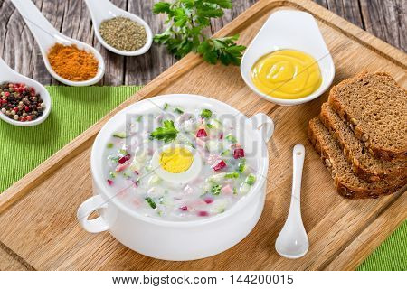 meat greens and vegetables cold No-Cook soup with greek yogurt in white cup with homemade bread spices and mustard in gravy boat on cutting board view from above close-up