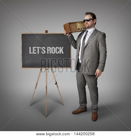 Lets rock text on blackboard with businessman holding radio